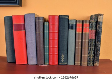 Antique books on old wooden shelf. Old books on yellow and claret background.
