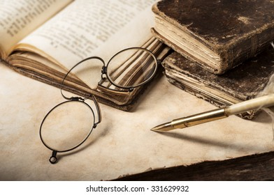antique books and spectacles on old parchment