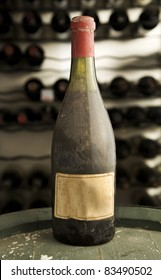 Antique bottle of wine, with an old blank label, on top of a wine vat in a cellar. This is known as a museum class wine.