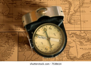 Antique brass compass on map background
