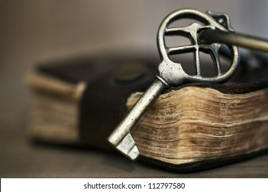 Antique brass key on old leather-bound book.  Shallow depth of field.