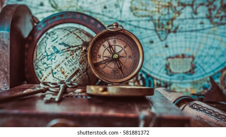 Antique bronze compass and globe sphere models on the ancient world map in vintage style picture.