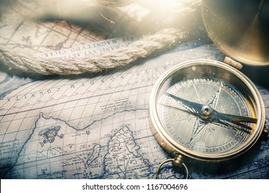 Antique bronze emblem compass, mini compass necklace pendant and binocular telescopes on ancient world map. (vintage style)