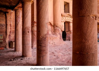 Antique building carved in sandstone with visible colums and open doors and windows in Petra - Jordan, Middle East