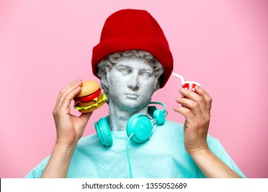 Antique bust of male in hat with cola drink and hamburger on pink background. Ready for summer vacation