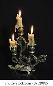 Antique candelabra with three melting candles on black background