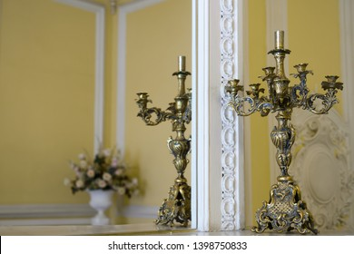 Antique candelabrum on mirror in the room. An ancient candlestick in the interior.