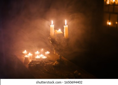 Antique candlestick in a mysterious atmosphere of smoke. The candle burns in darkness the night of secrets. Halloween ritual witch wizard occult spiriotic. Alchemy religion the witcher background