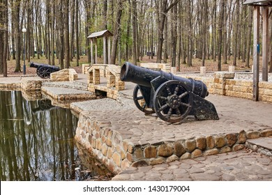 Antique cannon stands on the pier with paved paving stones against the background of the forest. Old cannon large. Ancient black cannon.