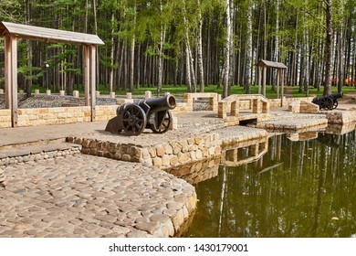 Antique cannons stands on the pier with paved paving stones against the background of the forest. Old cannon large. Ancient black cannon.