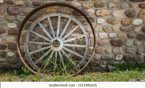 Antique cartwheel and iron rim near the stone wall of the tavern