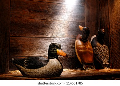 Antique carved wood hunting duck decoy and aged traditional vintage decoys in an old wooden hunter barn or cabin in soft diffused light