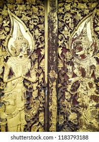 """Antique carving Thai pattern or Lai Thai """"Thep Pha Nom"""" decorated on the old wooden door of a building in Thai temple."""