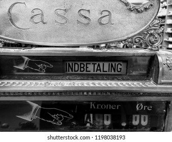 """Antique cash register with Italian """"Cassa"""" (cash register) and Danish """"Indbetaling"""" (payment), """"Kroner"""" and """"Øre"""" (DKK currency """"crowns"""" and """"ears""""), and 👉 (emoji hand pointing right)."""