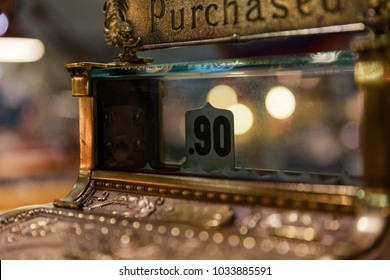 Antique cash register with ninety cents showing as a sale.