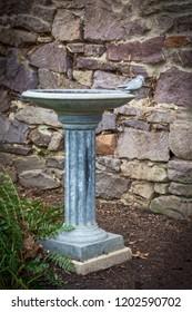 An antique cast iron birdbath along a rock wall in garden.
