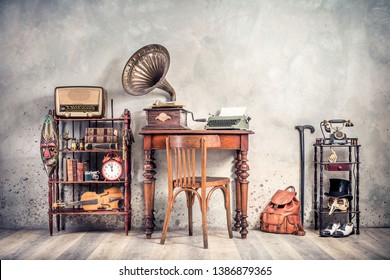 Antique chair, old typewriter, retro radio,  gramophone on wooden desk, books, clock, camera, binoculars, fiddle, keys on shelf, mask, cylinder hat, shoes, cane, backpack. Vintage style filtered photo