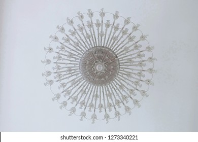 Antique chandelier made of glass and crystal hang from plain white ceiling at ballroom in beautiful palace for dancing party tonight is romantic decoration for girl or woman's dream