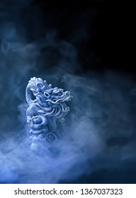 Antique Chinese dragon figurine. Chinese dragon statue in a smoke on black abstract background. figure of stone Chinese dragon. symbol of wisdom, good start, Imperial power. copy space
