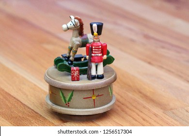 An antique Christmas musical box with a wooden toy soldier and rocking horse