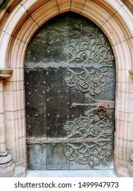 Antique church door entrance set in a stone wall with richly engraved and decorated wrought iron hinges. At Chester Cathedral in the city of Chester, Cheshire, England