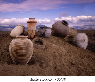 antique clay pots in a mound of sand