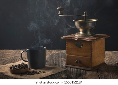 Antique coffee grinder with steaming coffee, and coffee beans