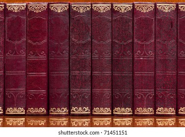 Antique collection of books bound in red leather with gilt writing on a reflective wooden shelf. With spaces for titles.