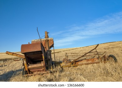 Antique combine left in a farm field