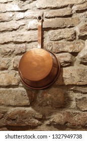 antique copper cookware on a brick wall