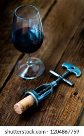 An antique cork screw with a cork stained with red wine and stamped '  on a dark wood table with a glass of red wine .