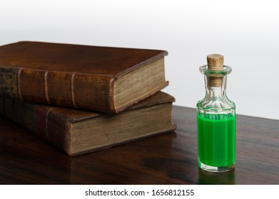 Antique corked crystal bottle with a mysterious glowing green liquid, is it poison or a magic potion created from the ancient leather bound books beside it.