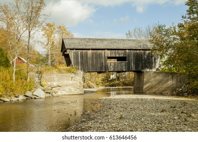 Antique covered wooden bridge with an American flag in Vermont, countryside