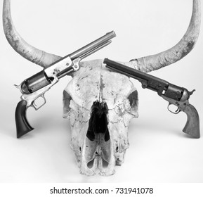 Antique cowboy pistols and cow skull in black and white.