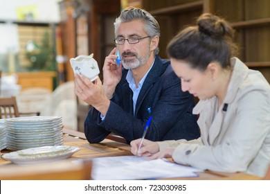 antique dealer inspecting object assistant making notes beside him