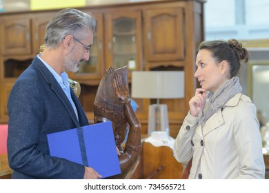 antique dealer looking at custoemrs wooden carving