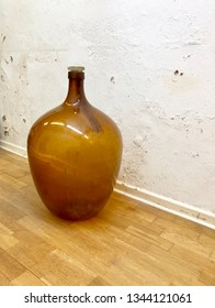 Antique demijohn in brown glass on wooden parquett floor against white weathered and plastered damp wall.