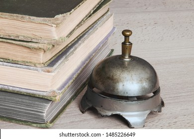 Antique desk bell beside an old stack of books; Simple arrangement of  vintage books and bell