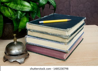 Antique desk bell beside an old stack of books; Simple arrangement of a pencil,  vintage books and bell