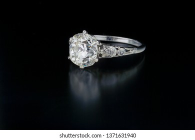 Antique diamond engagement ring with a one carat plus center stone and accent side diamond set in white gold.