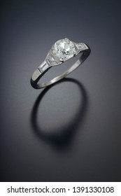 Antique diamond engagement ring with a one carat plus antique cut center stone and accent side diamonds set in platinum.