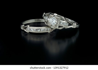 Antique diamond platinum engagement ring with a one carat plus center stone and accent side diamonds and an antique diamond platinum band lay on a black reflective background.