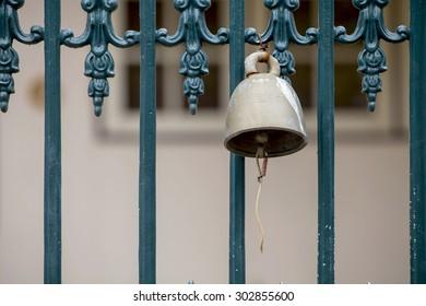 Antique door bell hanging on green gate