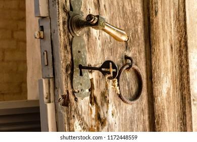 antique door key in wooden church door historic, blurred church interior