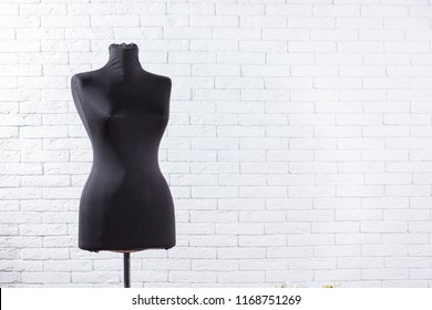 Antique dress form mannequin on white brick wall background