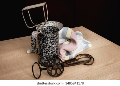 Antique egg beater, pitcher; and potato masher displayed with a tea towel; Display of several vintage items