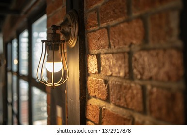 Antique electronic lamp, red wall lamp, high wall lamp, soft light.Red brick wall.Open chain, turn off the lights.hanging at the red brick wall in the building,Wall light brown brick,soft focus.