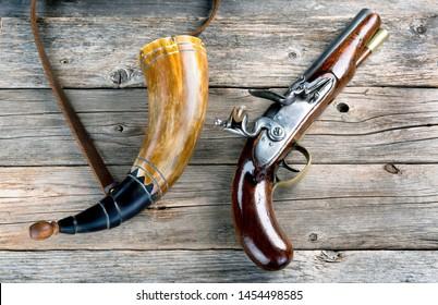 Antique English flintlock pistol and gunpowder horn made around 1800.
