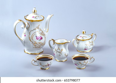 An antique faience coffee (tea) service with filled seagulls on a gray background.