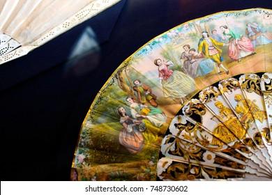 An antique fan lies on a table